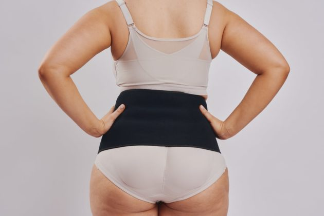 BodyAid black abdominal binder. Leonisa posture bra with rear criss-cross support bands in beige. Instant Leonisa booty boosting padded beige panties. Rear view.