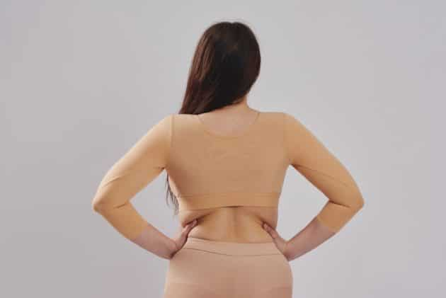 BodyAid arm lift compression crop in beige with 3/4 sleeves & posture support. Front three row hook and eye adjustment. Ideal for Brachioplasty and Liposuction to the arms. Rear view.