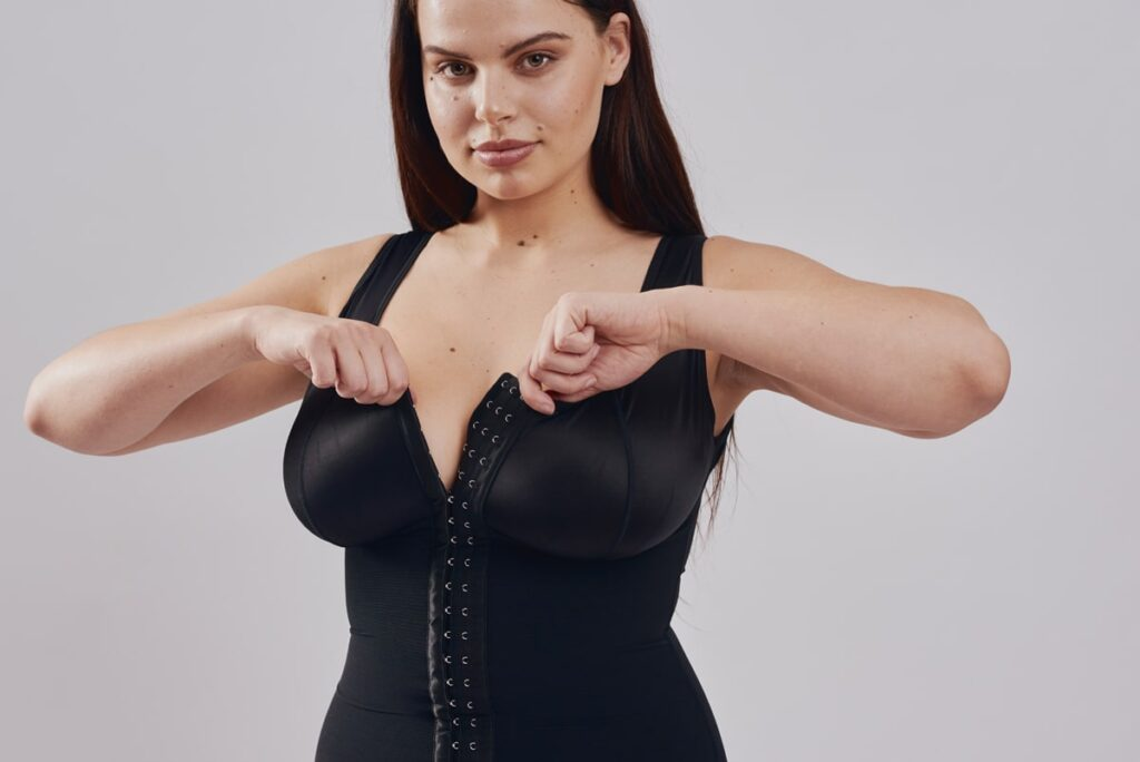 BodyAid black post-operative stage 1 bodysuit with built-in bra for extra support. Three row front hook and eye closure for multiple adjustments and control.