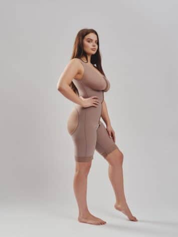 BodyAid natural post-operative comfort bodysuit with built-in bra for support. Three row front hook & eye closure for multiple adjustments & fit. Open crotch & non compressive butt lift shape support side view.