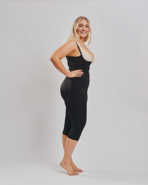 BodyAid Stage 1 Capri bodysuit in black with high back and adjustable straps. Features non brazilian butt lift shape support. BodyAid post surgery bra in beige. Side view.