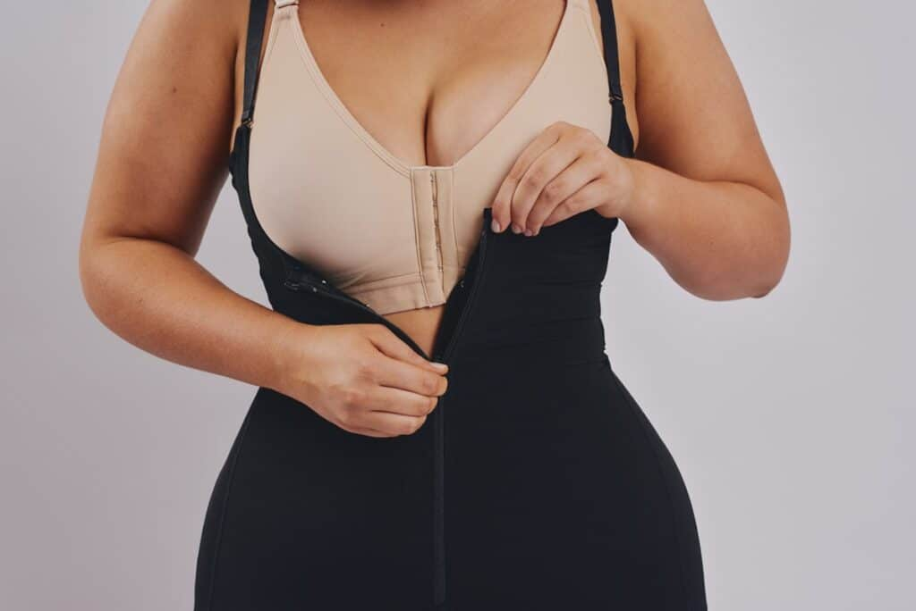 BodyAid Stage 1 Capri bodysuit shapewear in black with front zip teamed with beige BodyAid Stage 1 Front fastening post surgery Bra.