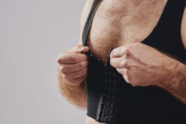 BodyAid chest compression binder in black. Features adjustable front hook and eye closure.