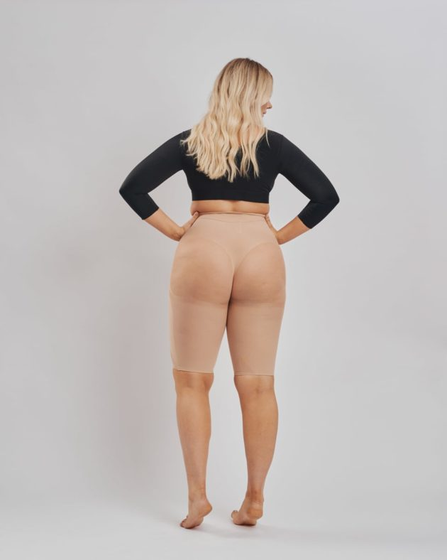 Well rounded Leonisa invisible butt lift shaper shorts in beige rear view. The backside is made with sheer mesh to avoid flattening. BodyAid arm compress crop in black.