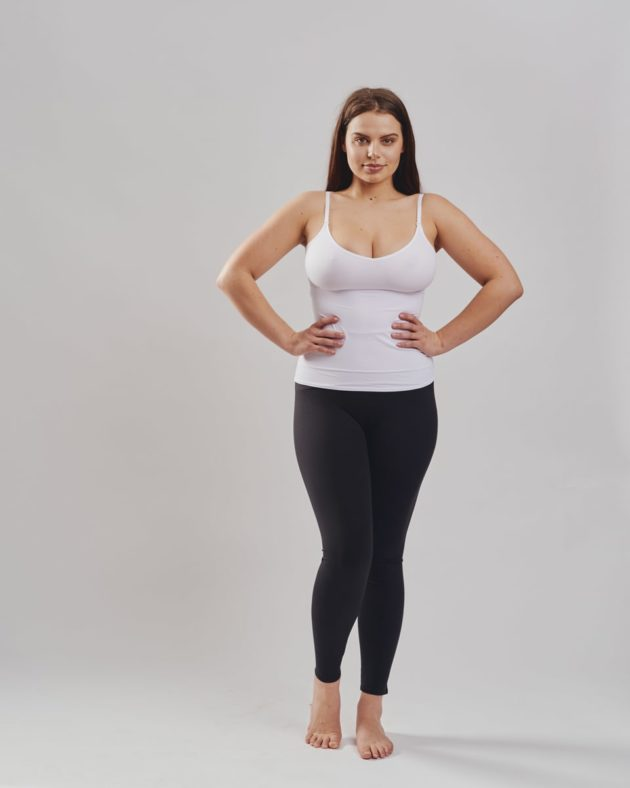 Leonisa mid-rise leggings in black with extra lower abdominal compression. Leonisa slimming compression tank in white.