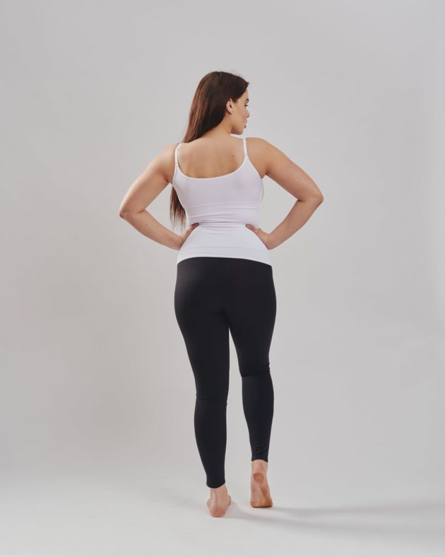 Leonisa mid-rise leggings in black with extra lower abdominal compression. Leonisa slimming compression tank in white. Rear view.
