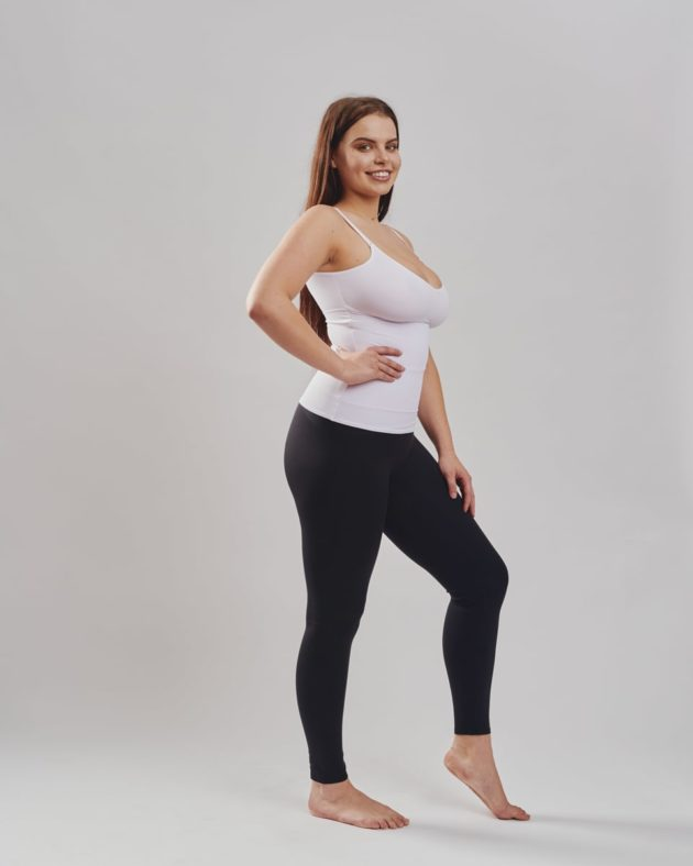 Leonisa mid-rise leggings in black with extra lower abdominal compression. Leonisa slimming compression tank in white. Side view.