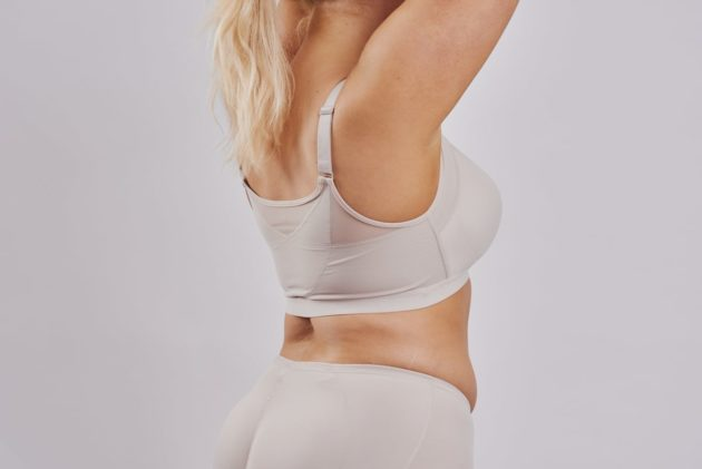 Leonisa posture bra with rear criss-cross support bands in beige. Front hook and eye closure and a smooth contouring finish. Instant Leonisa booty boosting padded beige panties. Rear view.