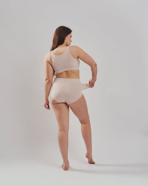 Leonisa firm compression postpartum panties with adjustable belly compression wrap in beige. Leonisa posture bra in beige. Rear view.
